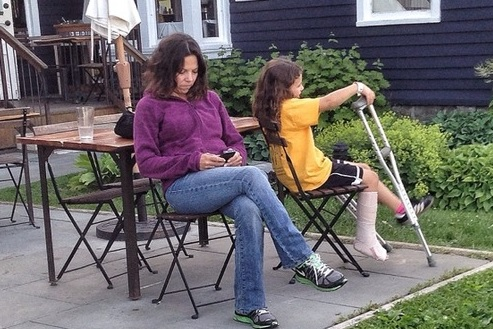 Parents on phones mum with daughter on crutches
