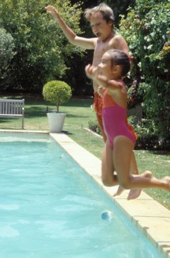 Swimming pool siblings jumping