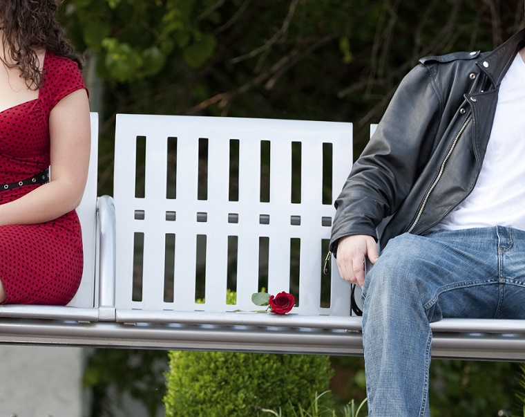 Young Couple Sitting At Opposite Ends Of Bench
