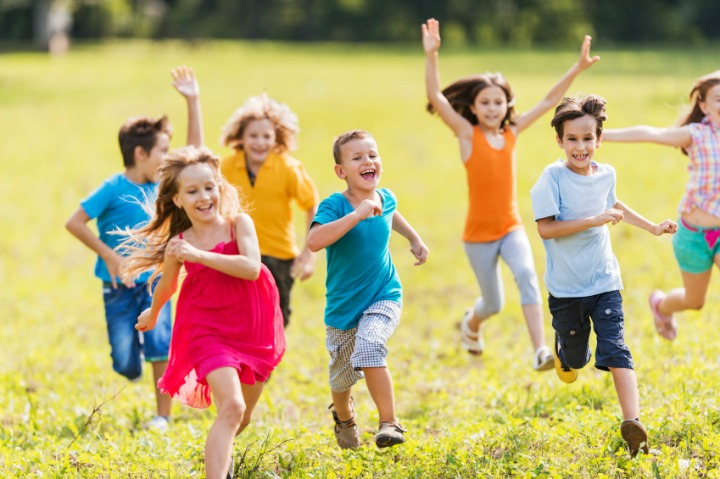 Playful group of children having fun in the park and running.