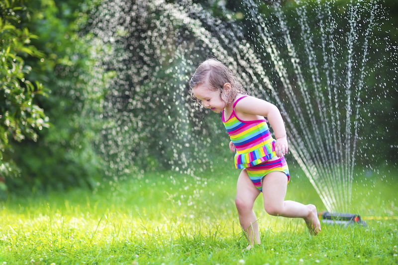 Little girl playing with garden sprinkler